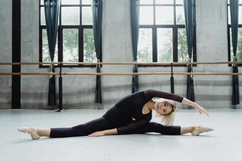 fit ethnic lady practicing ballet in studio